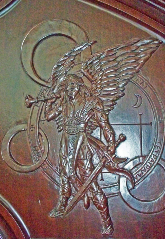 detailed carving of medieval warrior angel on a mahogany entrance door